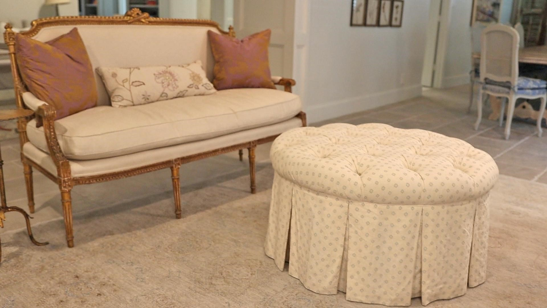 The patterned cream and blue french country furniture ottoman next to the solid settee by Amitha