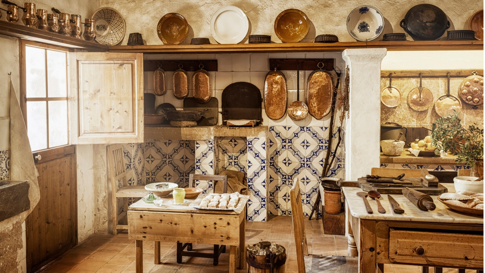 French country style kitchen with blue and white tiled walls, a natural wood-finished kitchen in a farmhouse style home that showcases copper kitchenware and an island nook seating area.