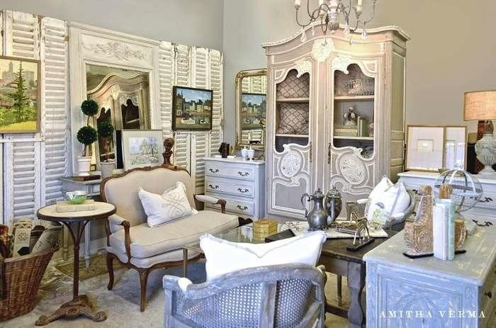 Vintage framed landscape artwork, chippy chalk finish painted side tables, upholstered settee and gray caned back accent chairs, trumeau mirrors, and antique decor collected in a farmhouse living room.