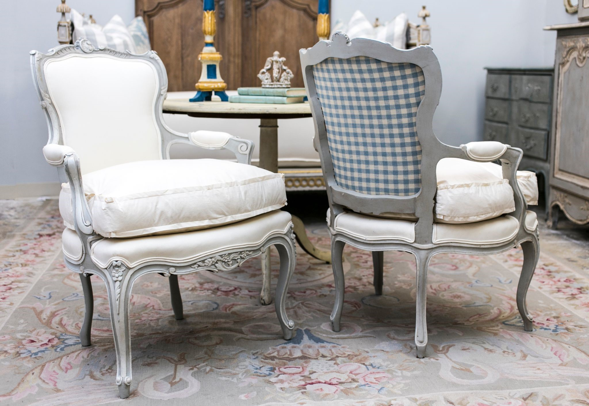 Two French provincial chalk painted, upholstered chairs in a farmhouse inspired home.