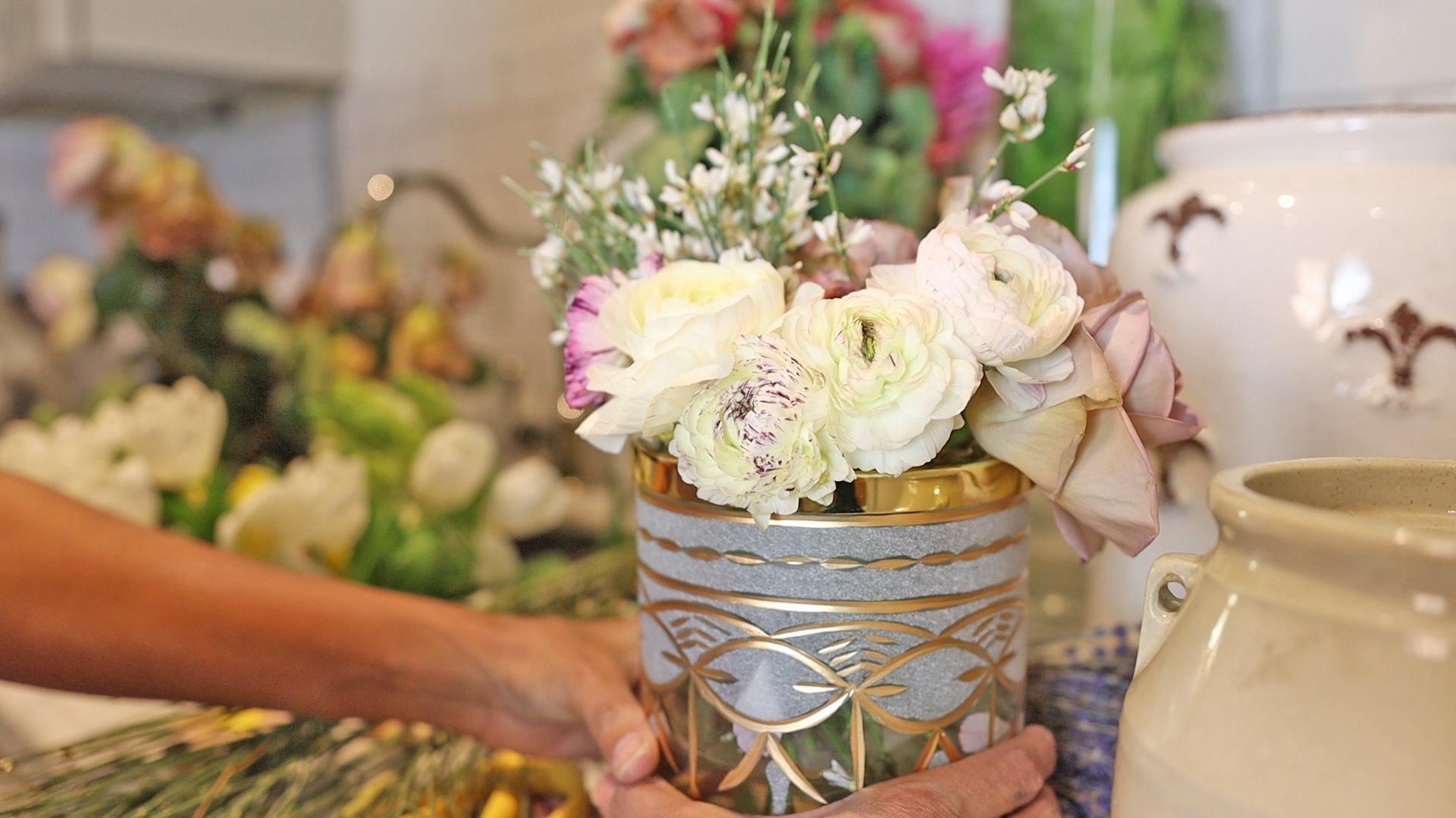 Roses, ranunculus, carnations, and genestra in the medium sized vase