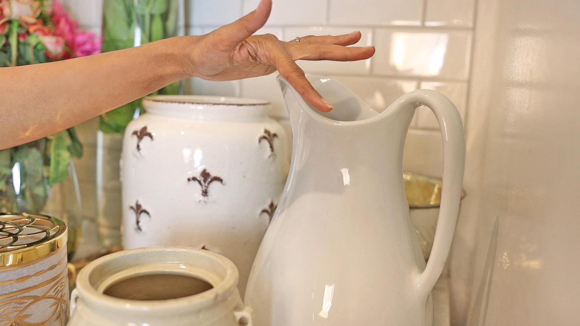 Amitha pointing to the wide mouth of a white ironstone pitcher