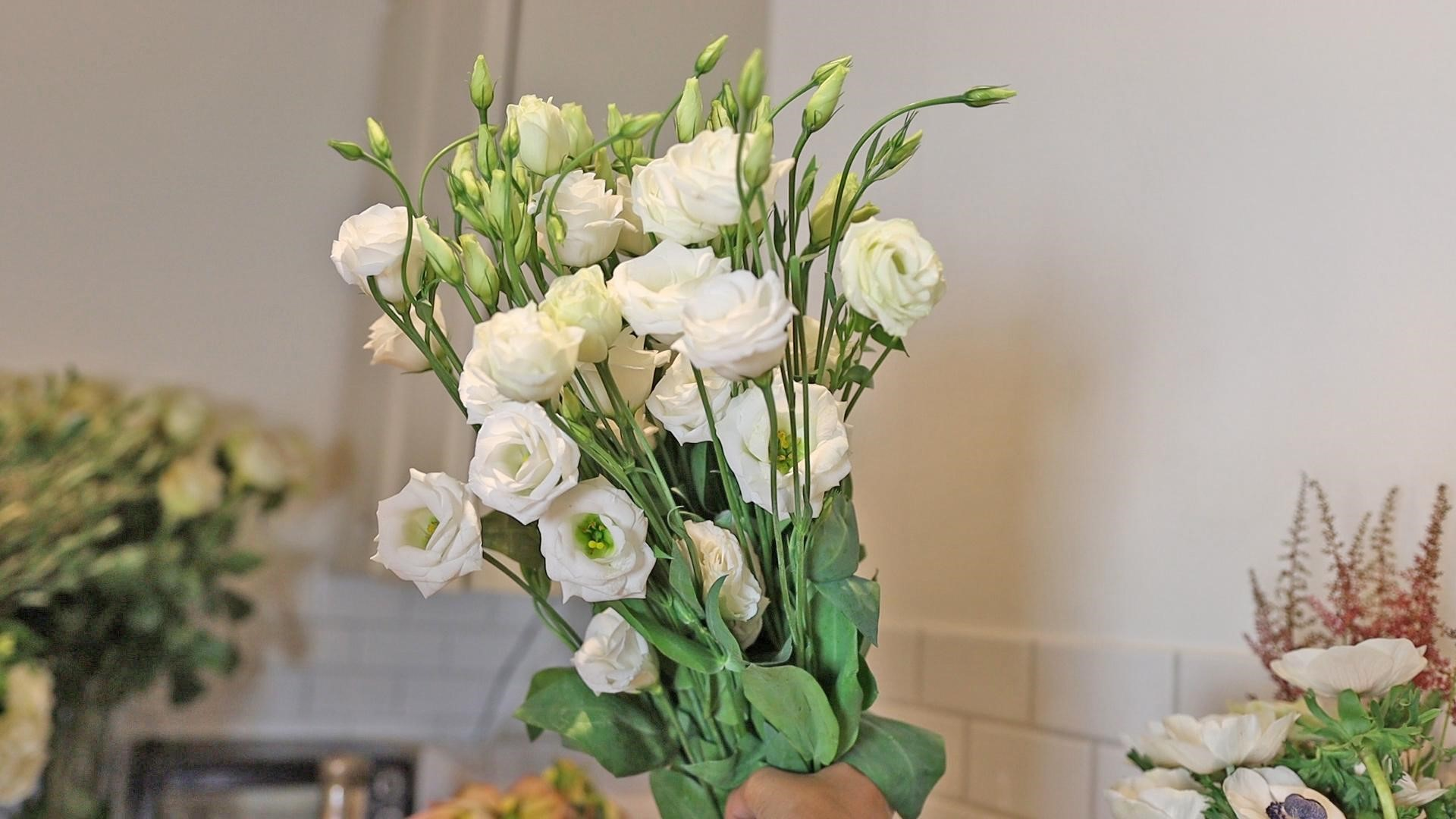 Amitha holding a fresh bunch of white lisianthus flowers