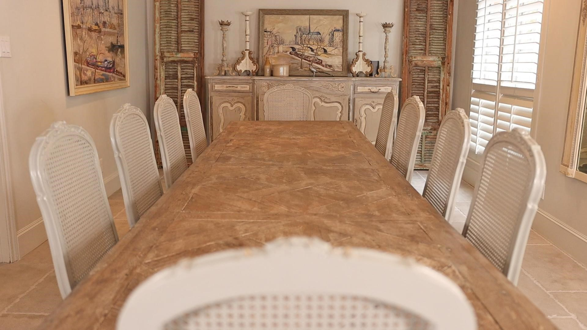 A long and narrow view of the large dining room space in French country style