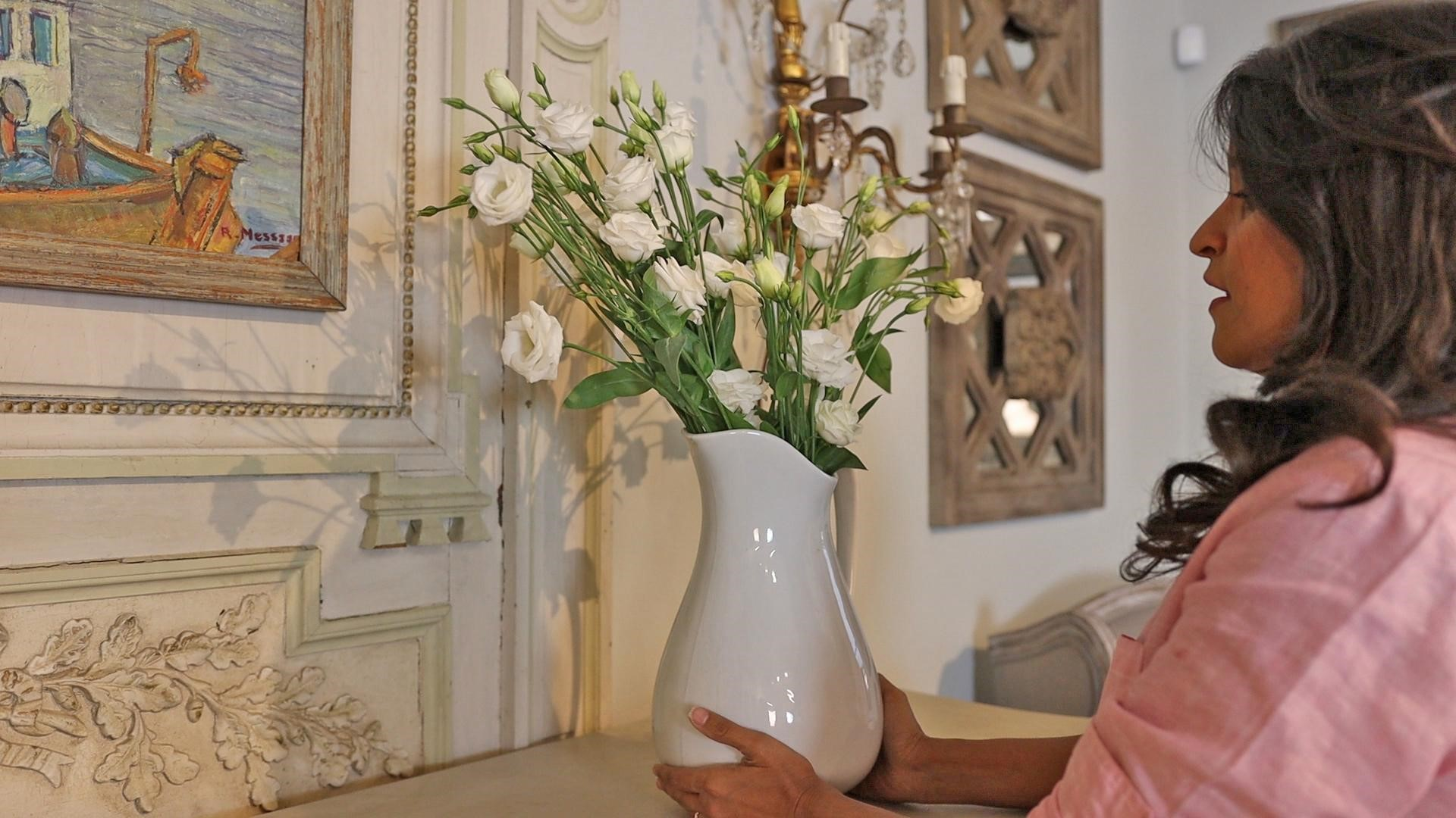 Amitha placing tall lisianthus flower arrangement in white ironstone pitcher on buffet