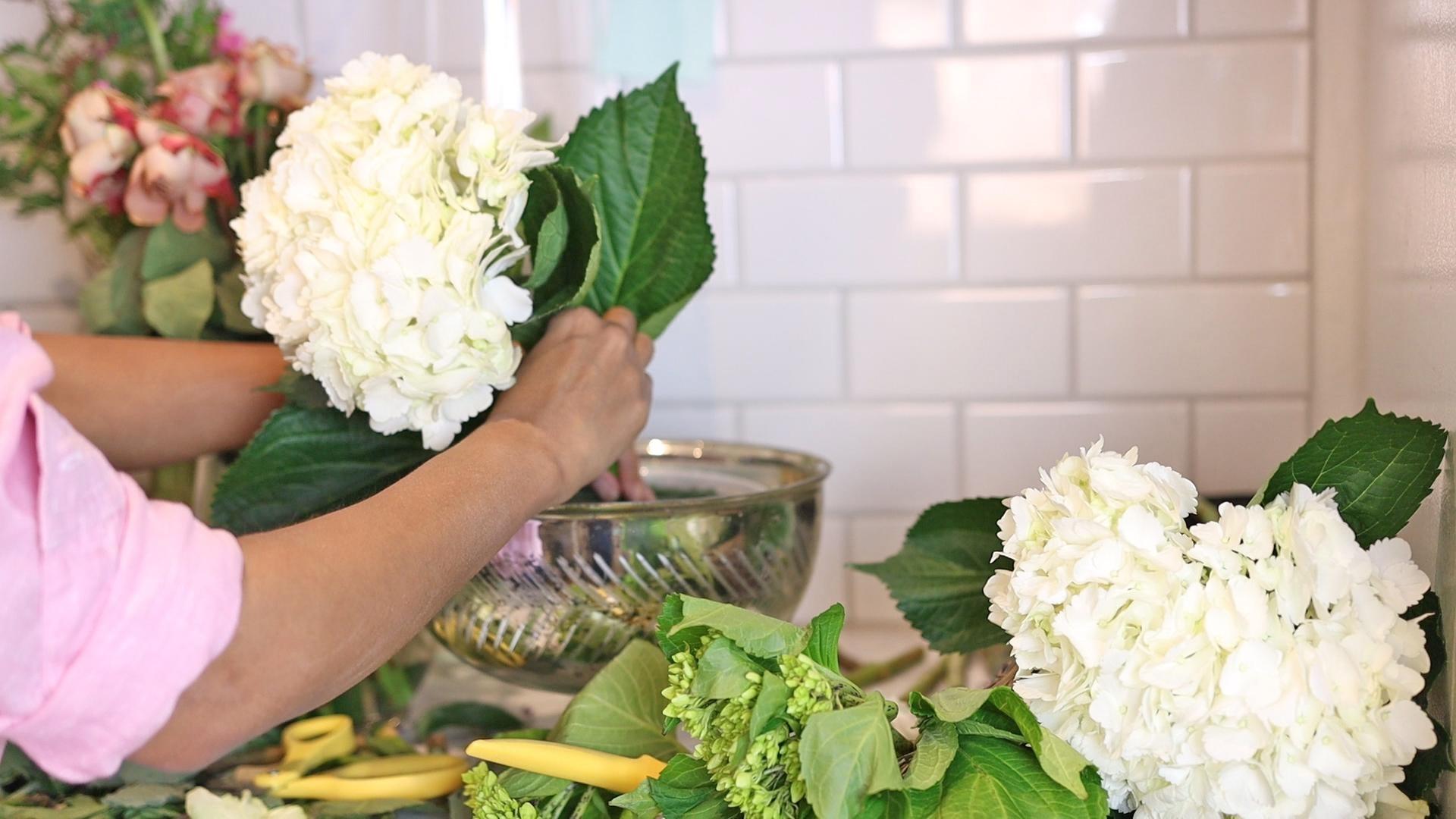 Amitha starts her bowl flower arrangement by placing large white hydrangeas