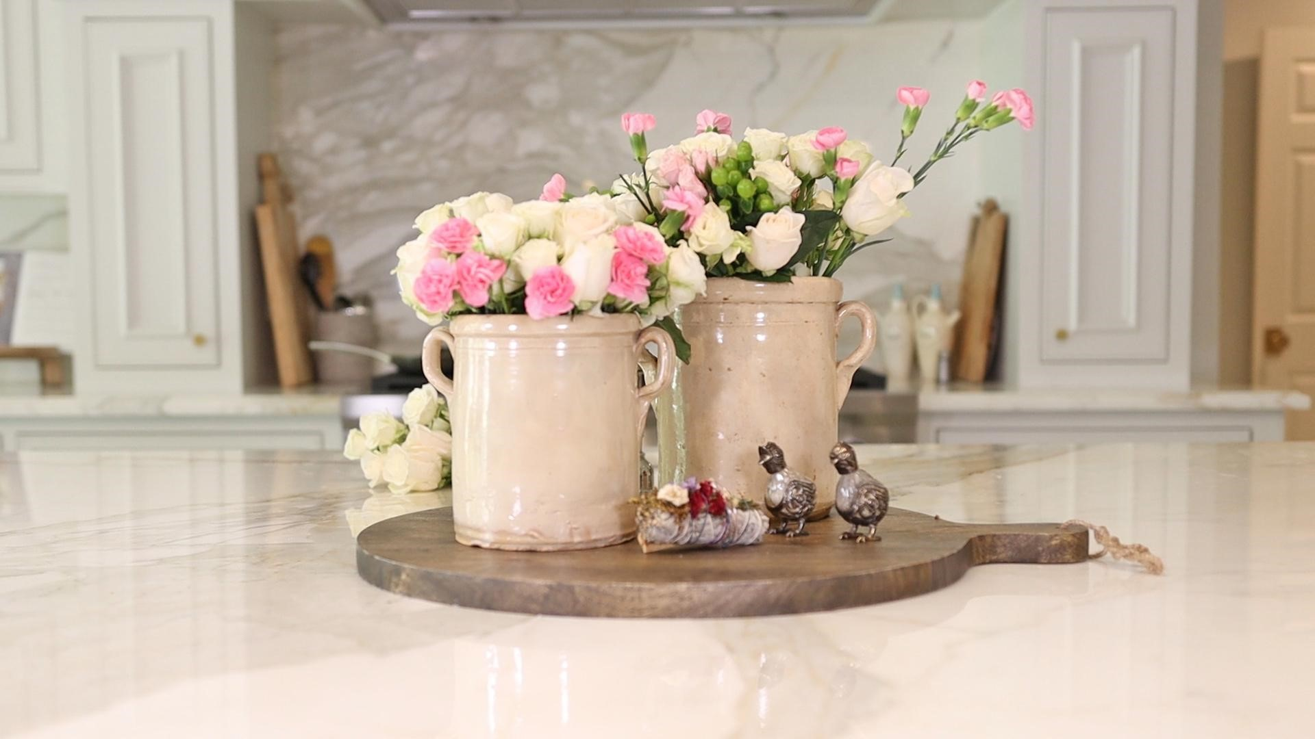 Two pink and white small floral arrangements in vintage french country containers on a breadboard in the kitchen.
