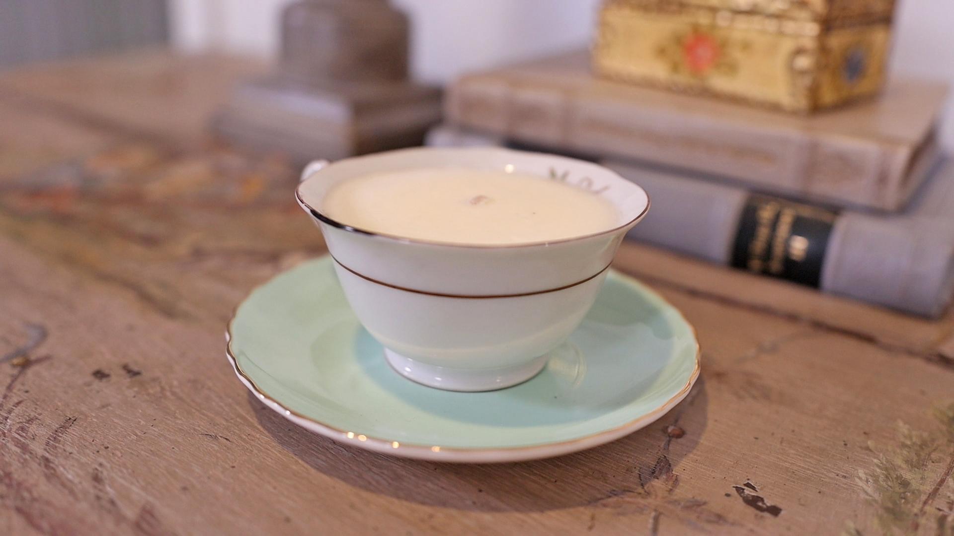 Artisan made teacup candle on a blue saucer.