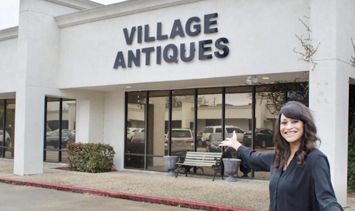 Amitha celebrates the opening of Village Antiques outside by the shop sign