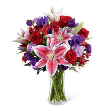 Stargazer lilies, Red Roses and alstromaria designed with lush accent flowers.