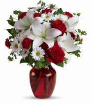 Love Bug..A Beautiful red vase filled with White Lilies, Red Roses, White daisies and lush greenery. A Favorite by all.