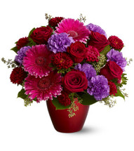 A mix of fresh red, hot pink and purple flowers such as roses, gerberas, Matsumoto asters and carnations is accented with greenery and is delivered in a red glass vase