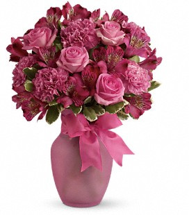 Arrangement includes pink alstroemeria, pink carnations, pink roses accented with variegated pittosporum. Delivered in a hot pink glass vase decorated with a hot pink ribbon