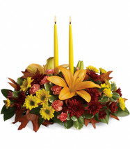 "The magnificent arrangement includes orange asiatic lilies, orange miniature carnations, yellow daisy spray chrysanthemums, burgundy cushion spray chrysanthemums accented with oak leaves and assorted greenery. Includes two 12"" yellow taper candles."