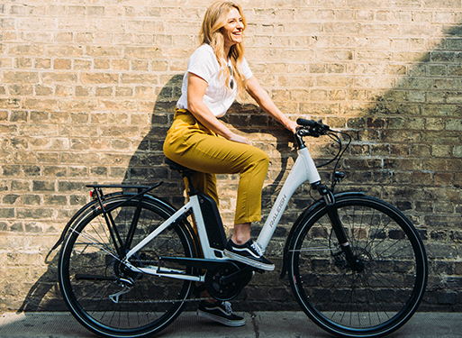 Trendy girl enjoying the city life on her electric hybrid bike