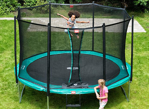 Little girl junping high in the sky on a Berg trampoline while her friend is watching