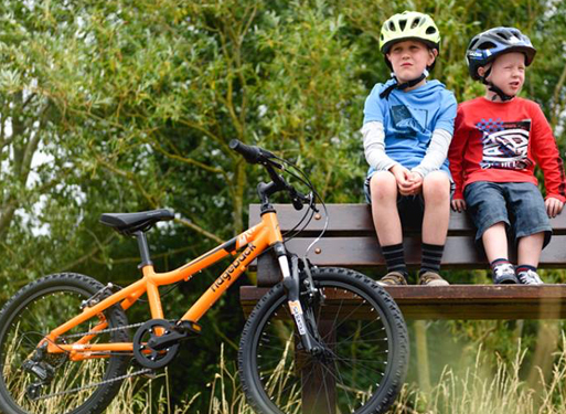 2 boys sitting on a bench beside their Ridgeback bike