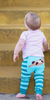 """Can't stop, won't stop grinning.  We've seen far too many diaper-bottomed tots squeezed into skinny jeans. (And we're only talking about this morning.) Whatever happened to comfort for the under 2 set? You know, leggings stretchy enough for wriggling and — dare to dream — fitting over cloth diapers. Yeah, it stumped us too, so we made our own, with original artistic """"doodles"""" on the bum, just because it makes us happy. (You're welcome. We love you, too.) • Cozy and soft construction with reinforced seams • Generous cut 'cause baby's got back • Adorably original designs (seriously, there are no words) • A percentage of every sale goes to supporting children in need • 70% polyester / 30% elastane • Machine wash with like colors, dry flat"""
