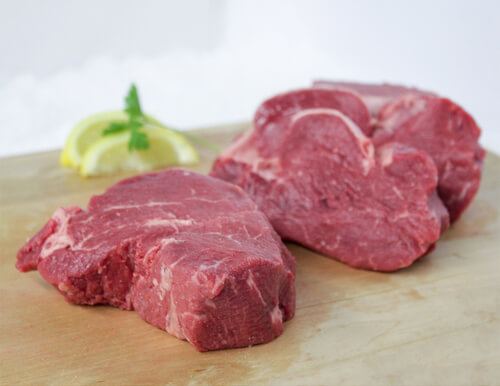 Three raw filets and lemon wedge