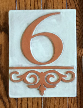 """GRANDE NUMBER TILE  This is a grande and beautiful tile.  It is 6h x 8w x 1/2"""" thick. It is shown in a standard off-white glaze with exposed terracotta numbers and design flourish.  Size will vary slightly with drying and kiln firing."""