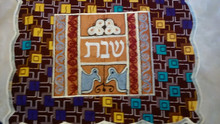 "One-of-a-kind challah covers crafted by the Tiferet Israel community in Sefwi Wiawso, Ghana. They are truly beautiful crafts, with embroidery and pieced African fabrics surrounding the Hebrew word ""Shabbat"" in the center. As no two are exactly alike, bulk orders will be comprised of assorted colors and patterns.                                                                                                          Proceeds from the sale of the challah covers benefit the Jewish community of Ghana."