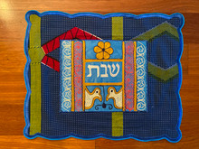 """-of-a-kind challah covers crafted by the Tiferet Israel community in Sefwi Wiawso, Ghana. They are truly beautiful crafts, with embroidery and pieced African fabrics surrounding the Hebrew word """"Shabbat"""" in the center. As no two are exactly alike, bulk orders will be comprised of assorted colors and patterns.                                                                                                          Proceeds from the sale of the challah covers benefit the Jewish community of Ghana.Type a description for this product here..."""