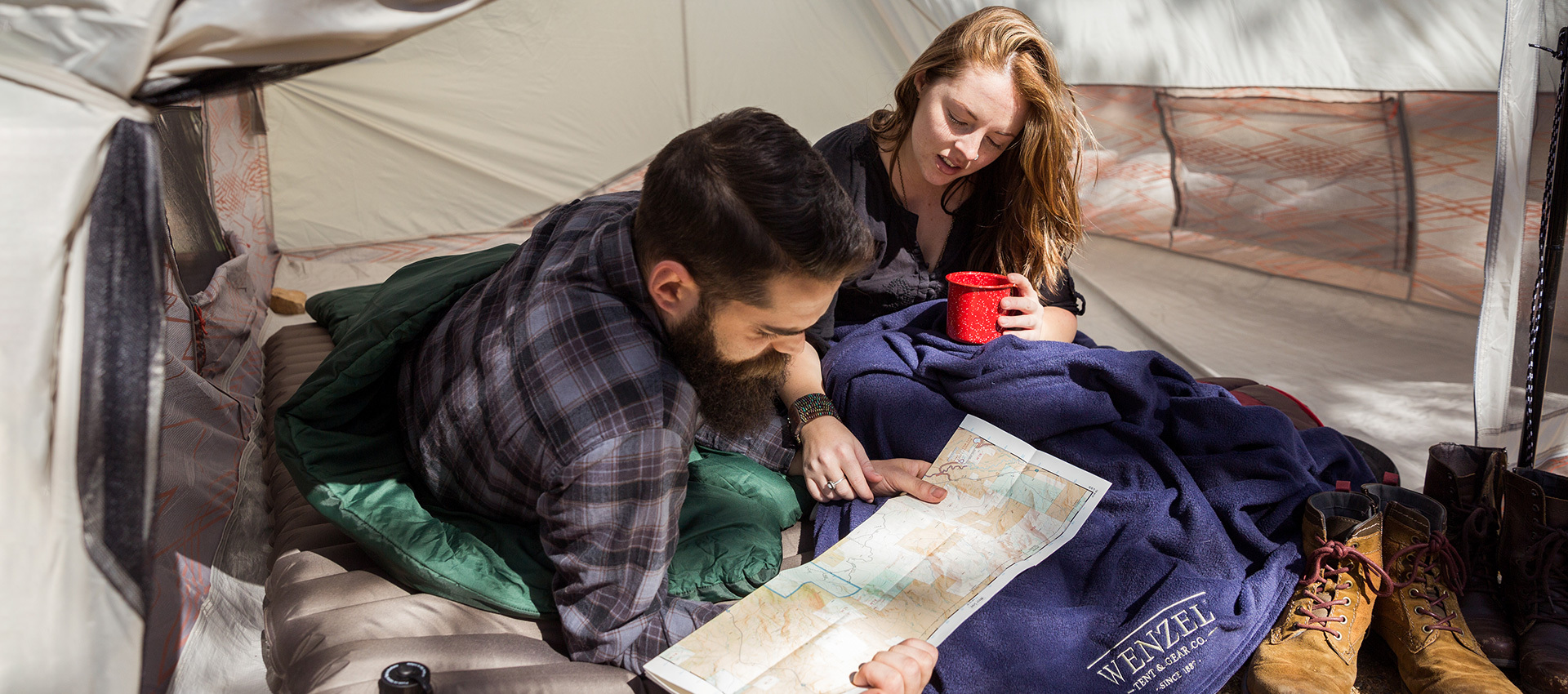 Couple reading a topo map in their tent