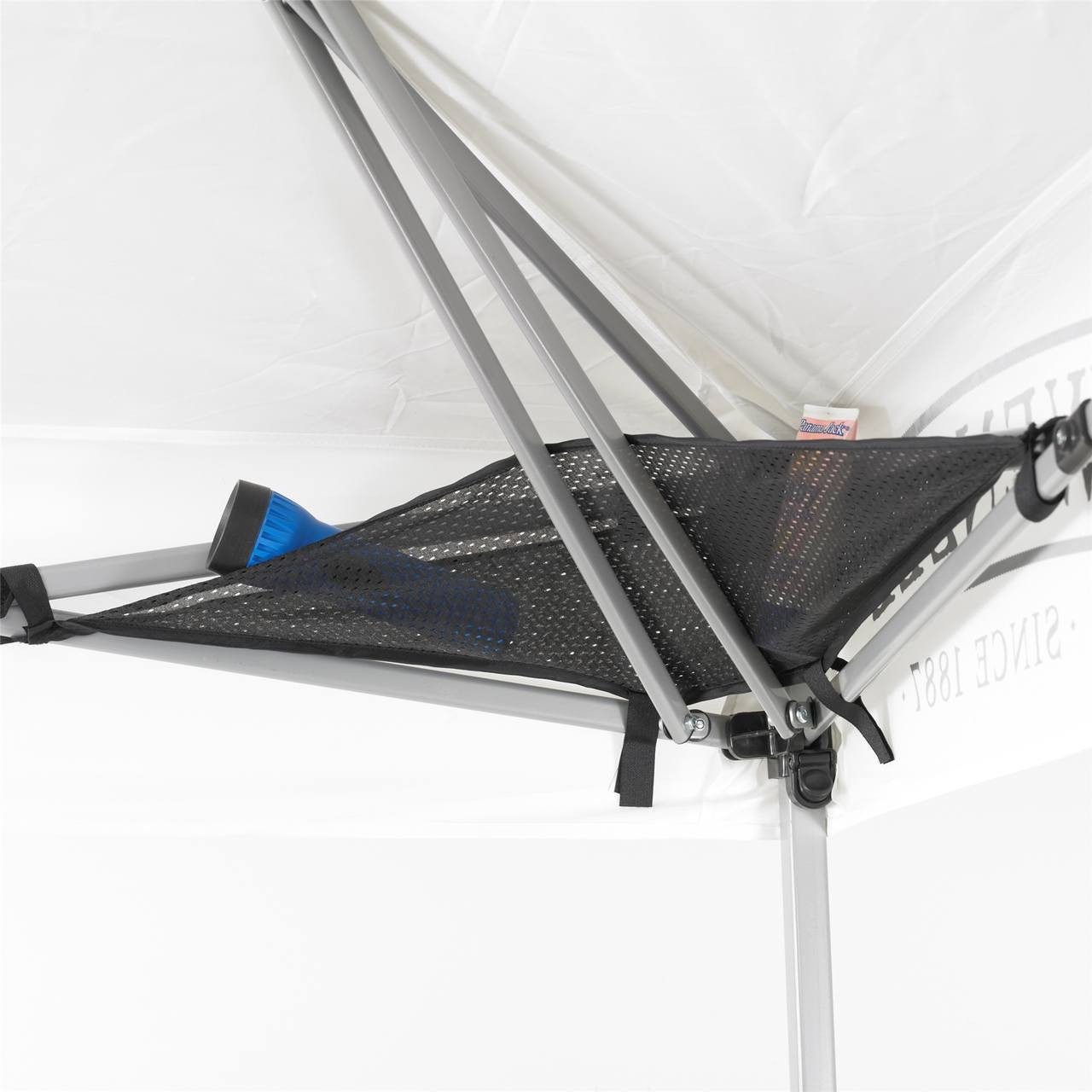 Close up view of a top corner in the Wenzel Smartshade Canopy 10'x10' with the mesh storage platform showing a flashlight and snacks stored