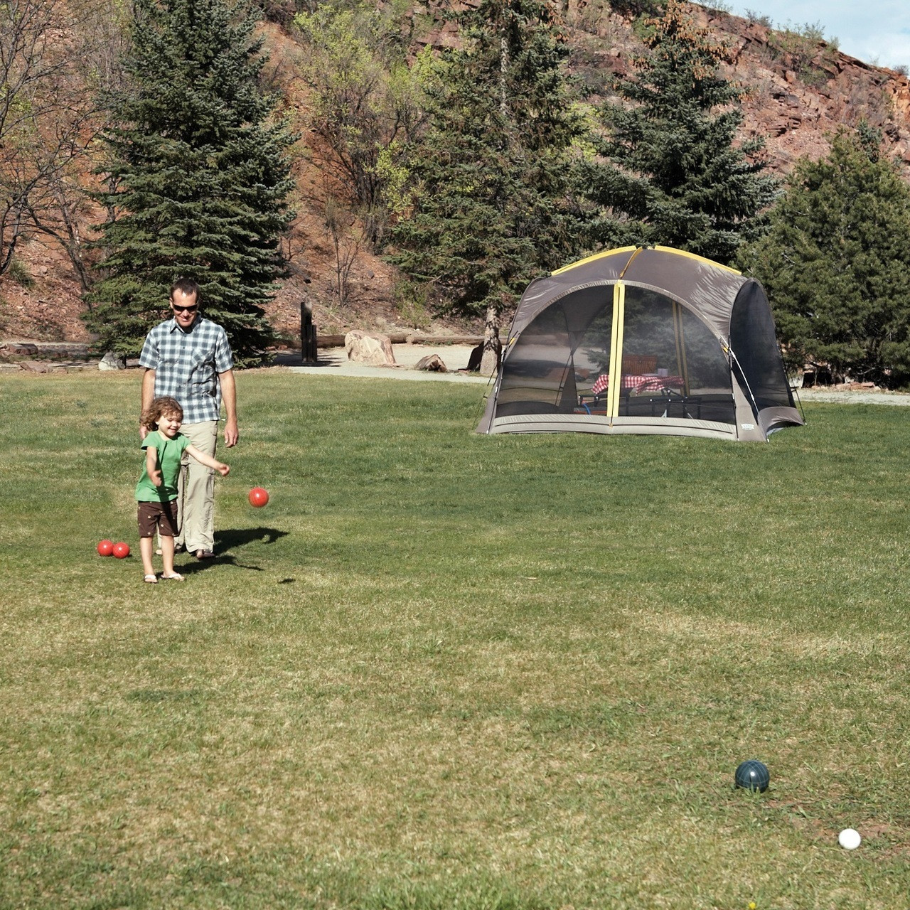 Man and his child outside of a setup Wenzel Sun Valley shelter playing Bocce ball