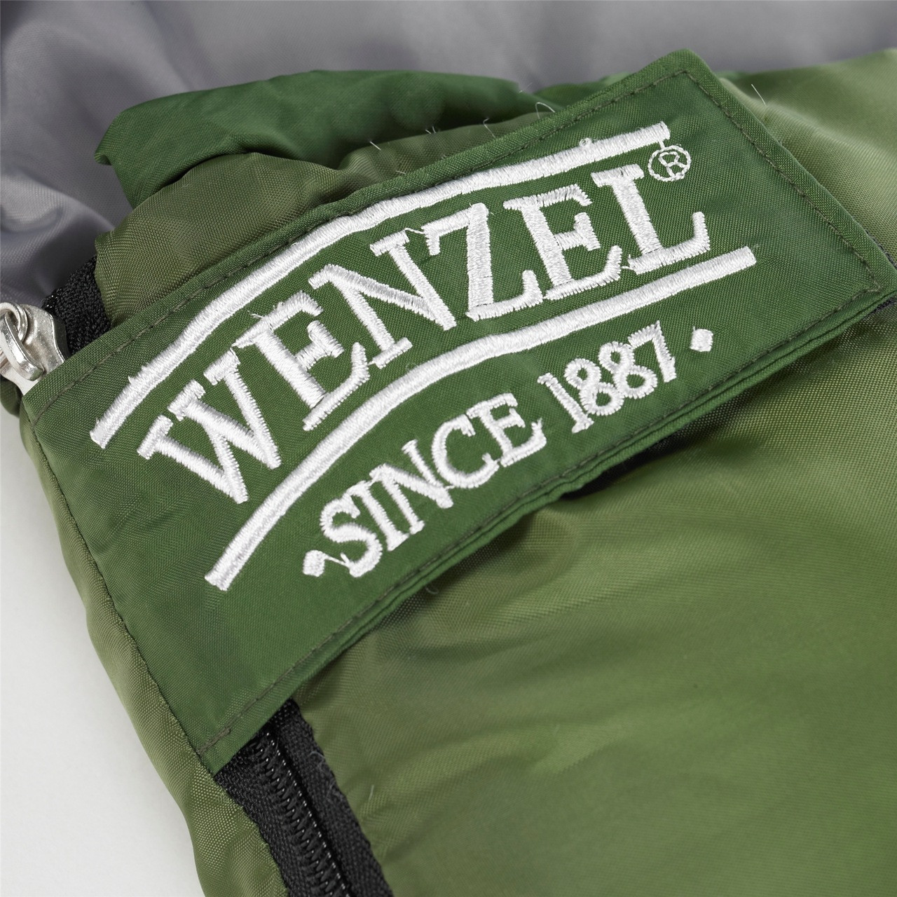 Close up view of the Velcro latch below the zipper on the Wenzel Kids Backyard 30 degree sleeping bag, green