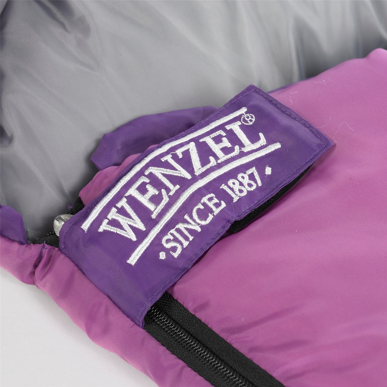 Close up view of the Velcro latch below the zipper on the Wenzel Kids Backyard 30 degree sleeping bag, purple