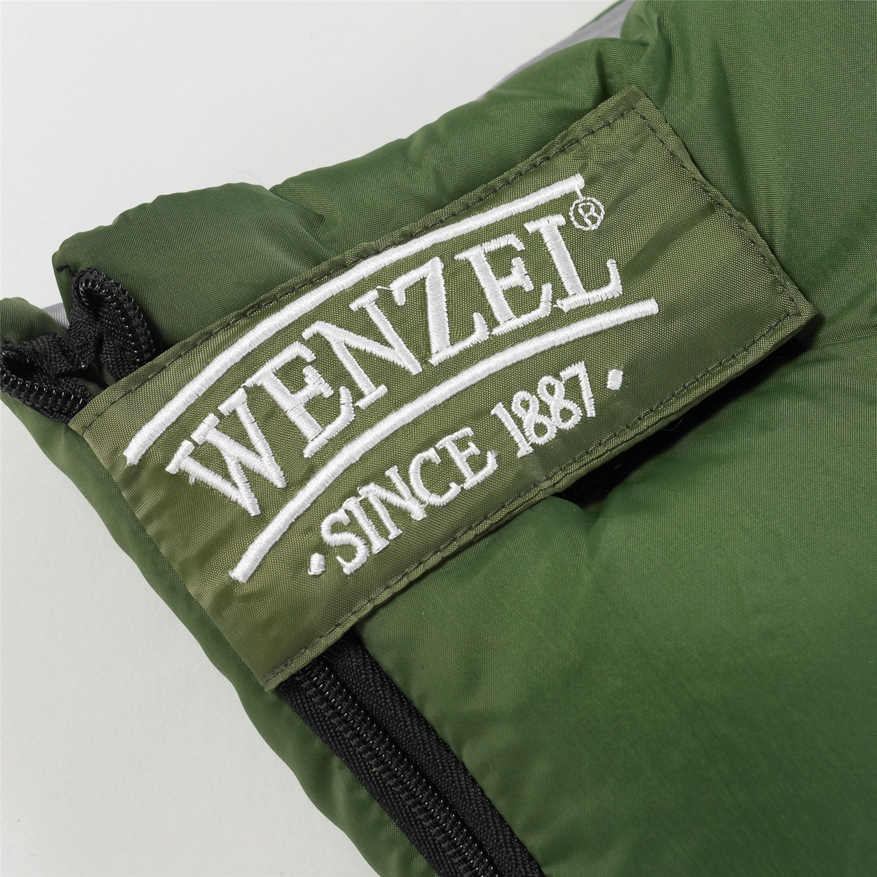 Close up view of the Velcro latch over the zipper on the Wenzel Kids Summer Camp 40 degree sleeping bag, green