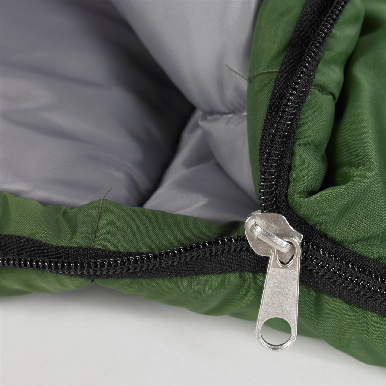 Close up view of the zipper partially unzipped on the Wenzel Kids Summer Camp 40 degree sleeping bag, green