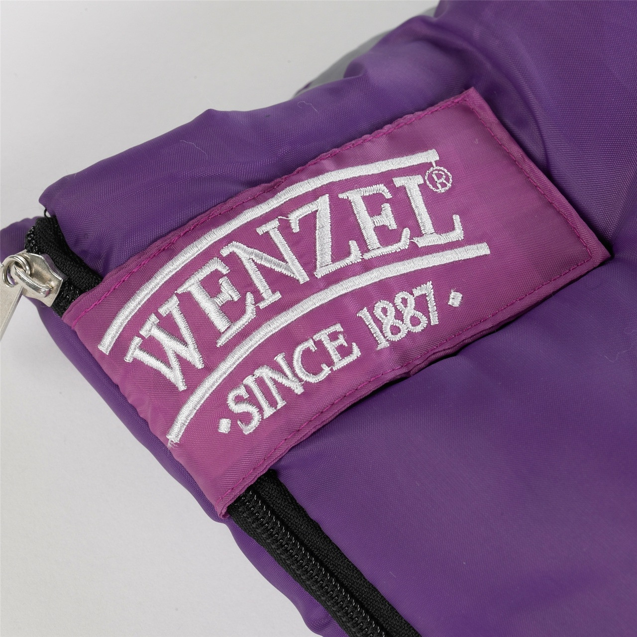 Close up view of the Velcro latch over the zipper on the Wenzel Kids Summer Camp 40 degree sleeping bag, purple