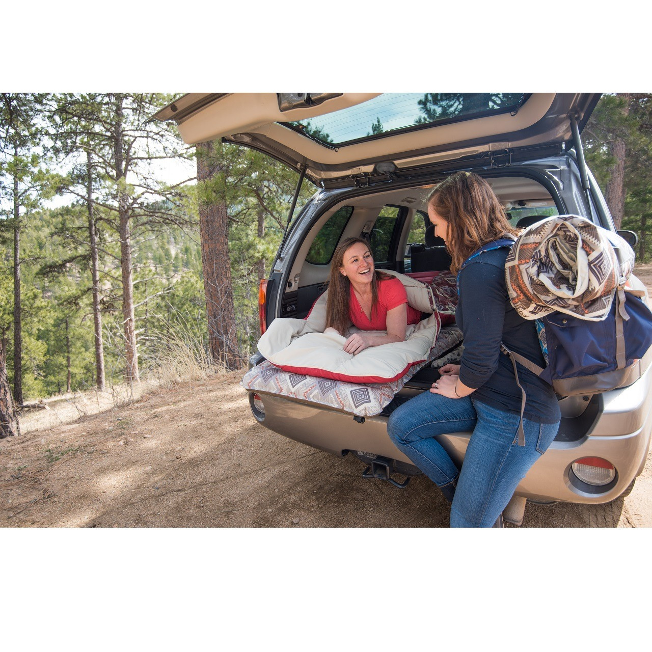 Woman laying in the back of a car on a Wenzel sleeping pad in a Wenzel Pop-Top sleeping bag talking to another woman outside the car