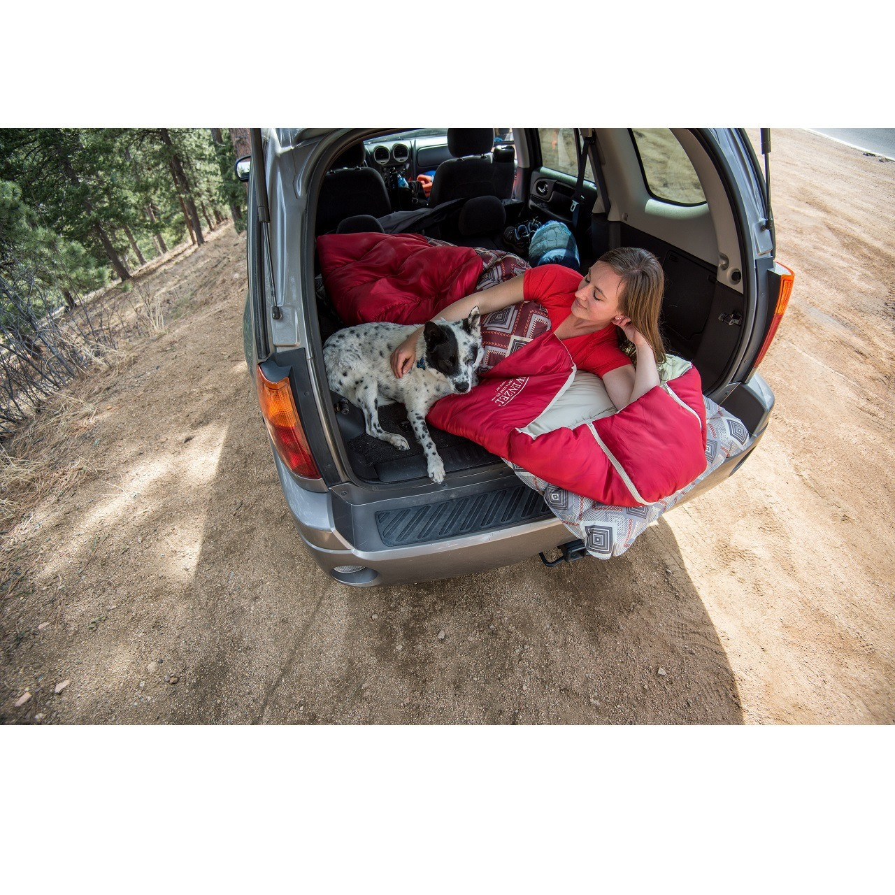 Woman laying in the back of a vehicle on a Wenzel sleeping pad in a Wenzel Pop-Top sleeping bag petting her dog laying near her