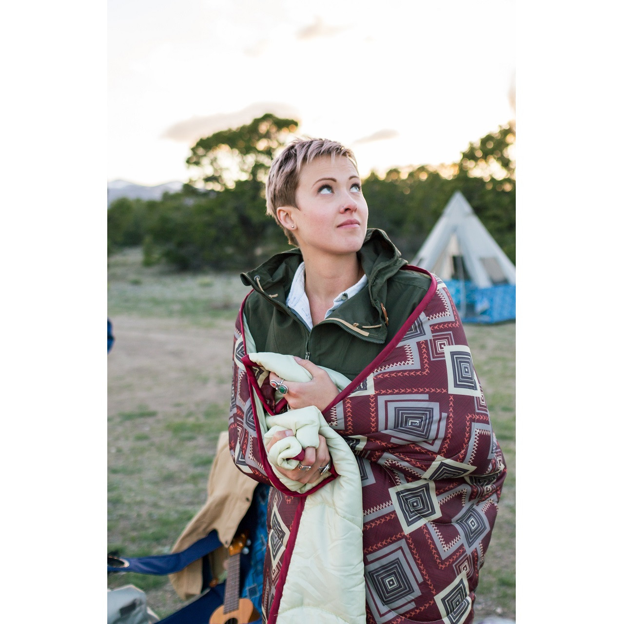 Woman standing outside in a field with a Wenzel Camp Quilt wrapped around her