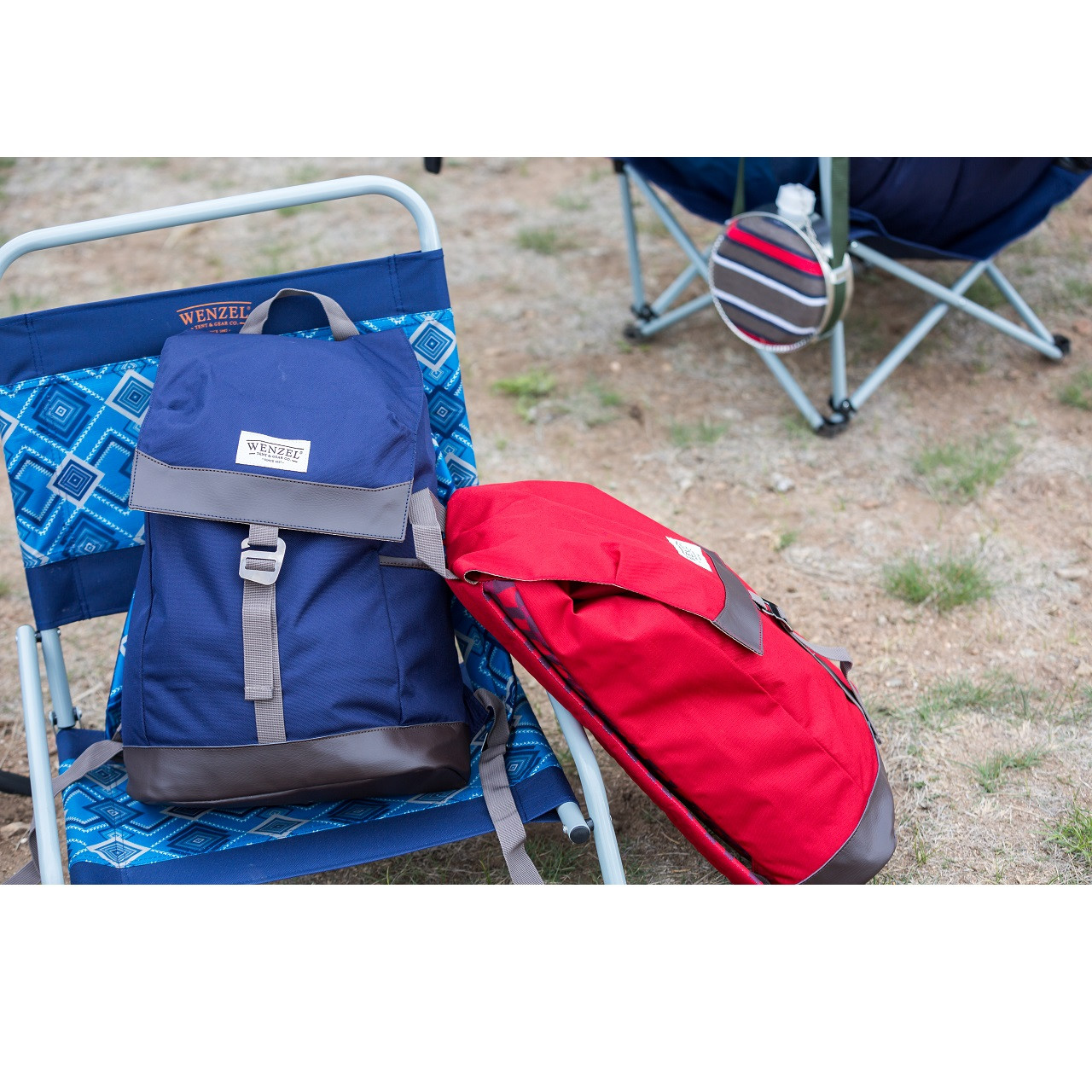 Two Wenzel Stache 20 backpacks, red and blue, sitting on a Wenzel chair outside