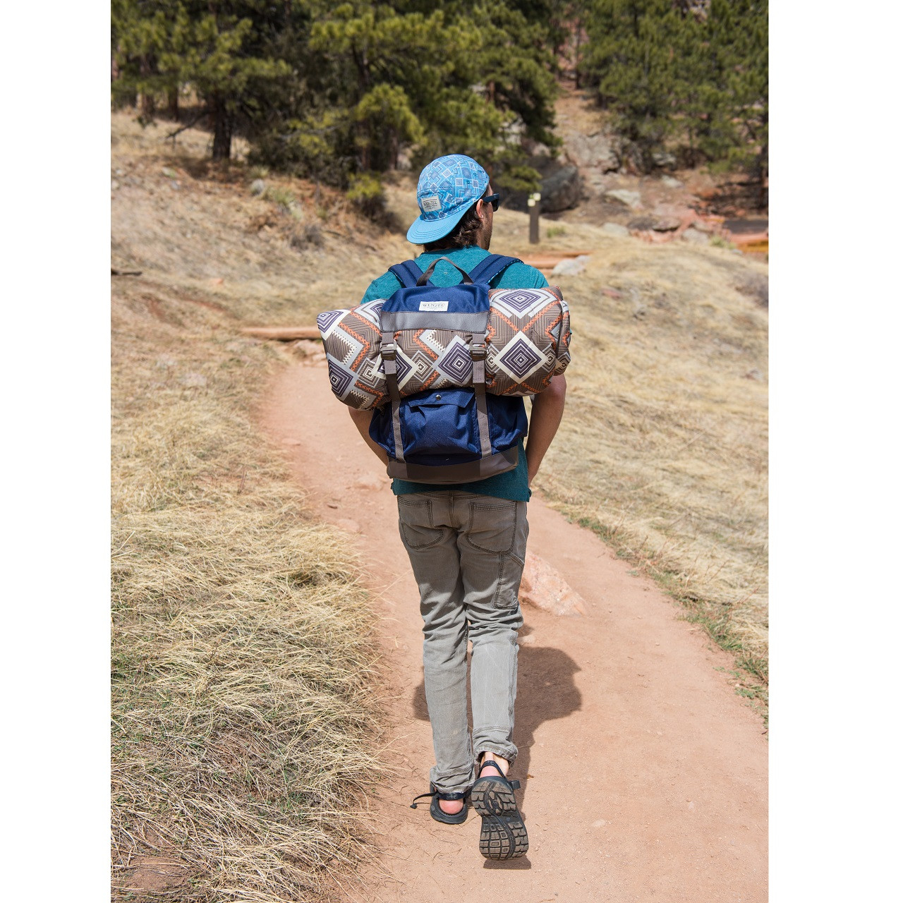 Back view of a man walking outside wearing a blue Wenzel Stache 28 backpack