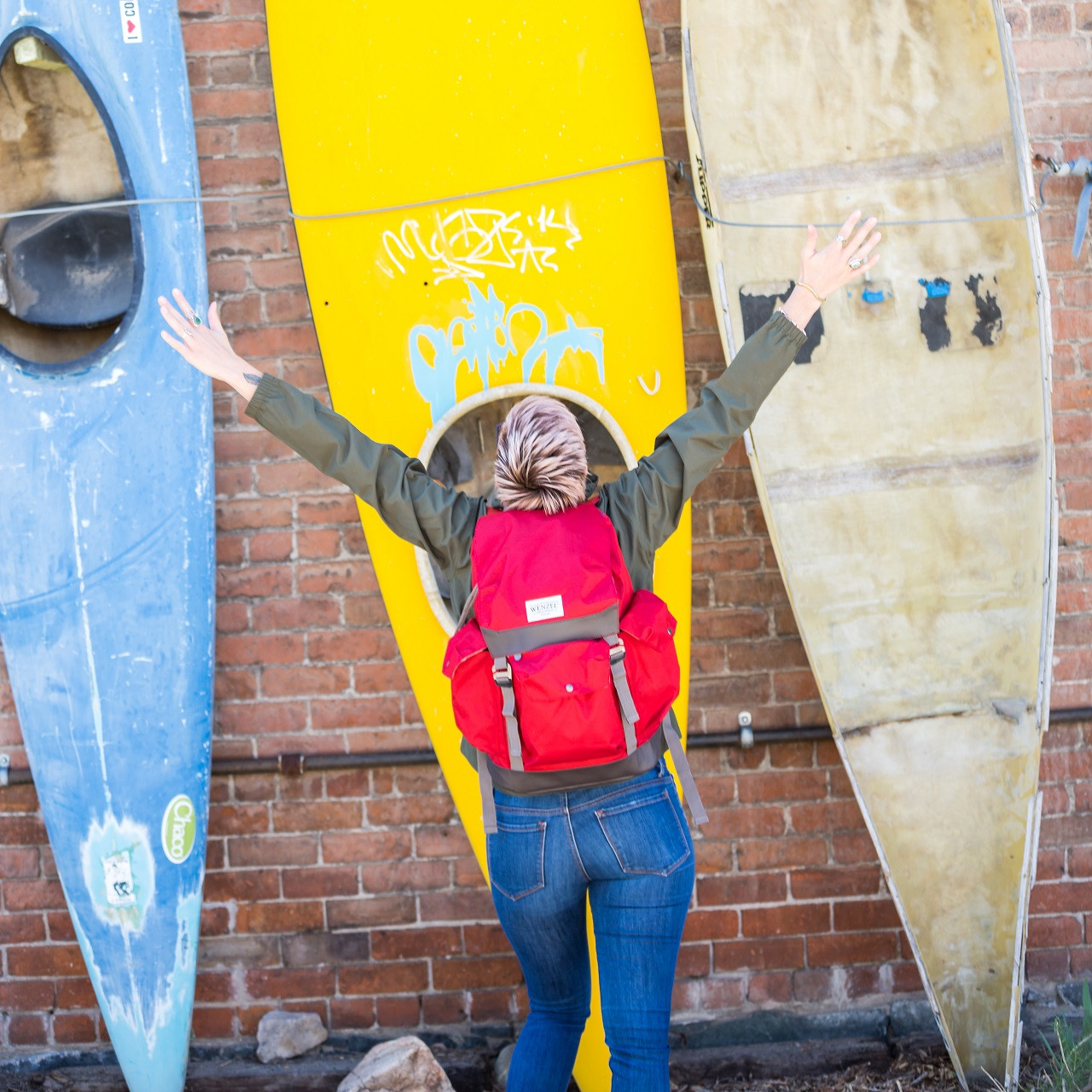 Back view of a woman standing outside near kayaks wearing a red Wenzel Stache 28 backpack