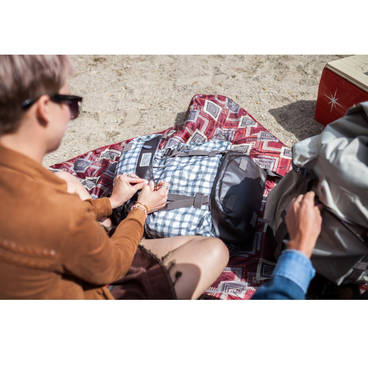Woman sitting outside on the ground on a Wenzel camp blanket closing the main compartment strap on a Wenzel Boulderdasche 33, white and gray plaid