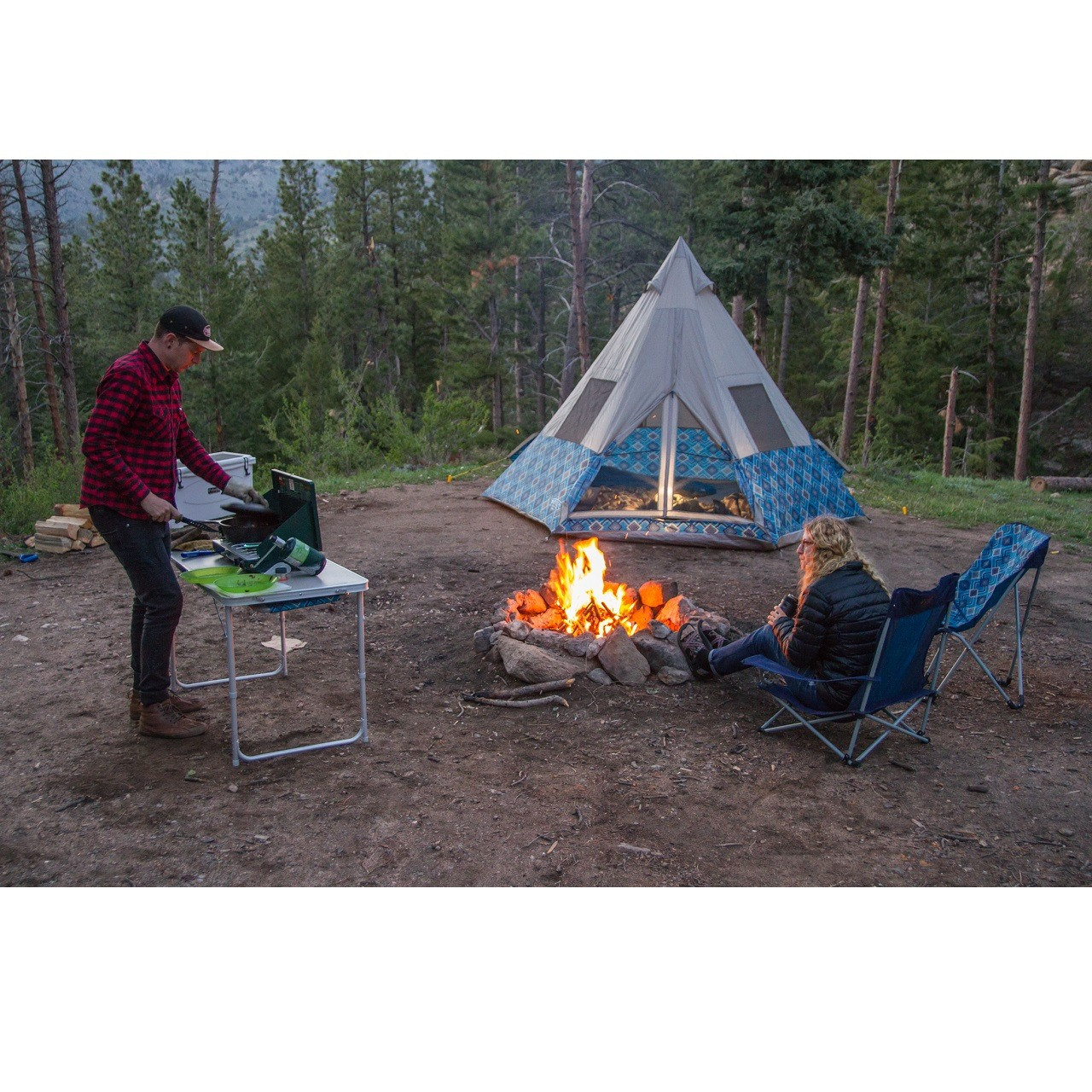 Man sitting outside of a Wenzel tent cooking on a stove with a woman sitting in a Wenzel Low Rise Quad Chair near a fire