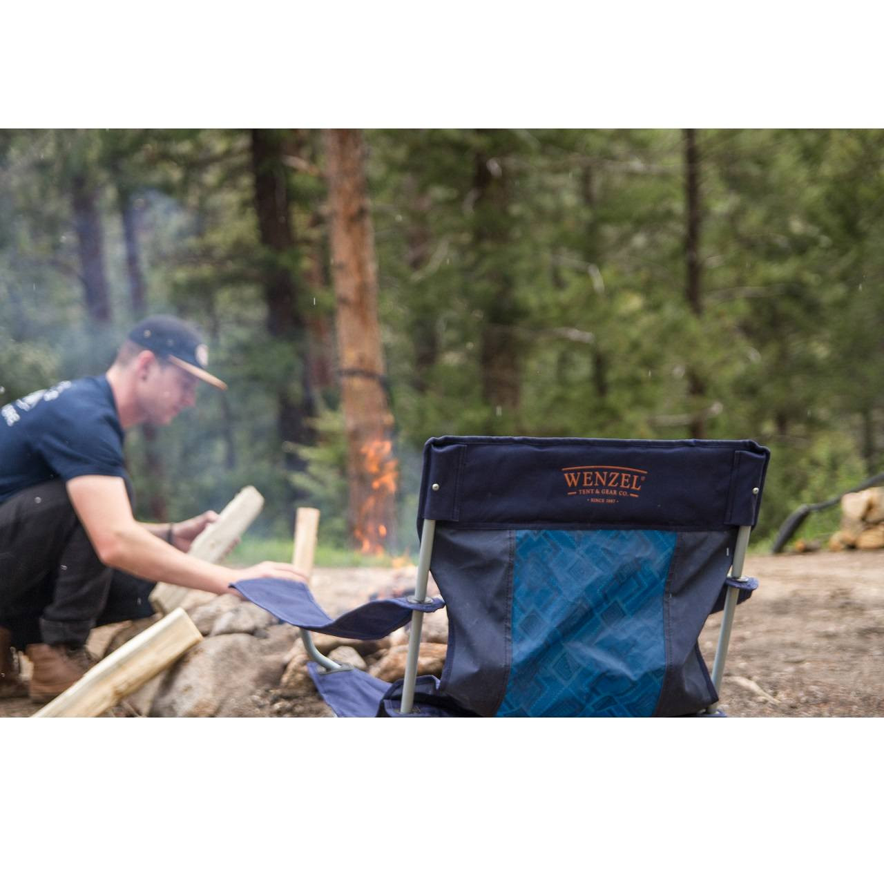 Man outside putting wood onto a fire with a Wenzel Quad Chair setup next to him