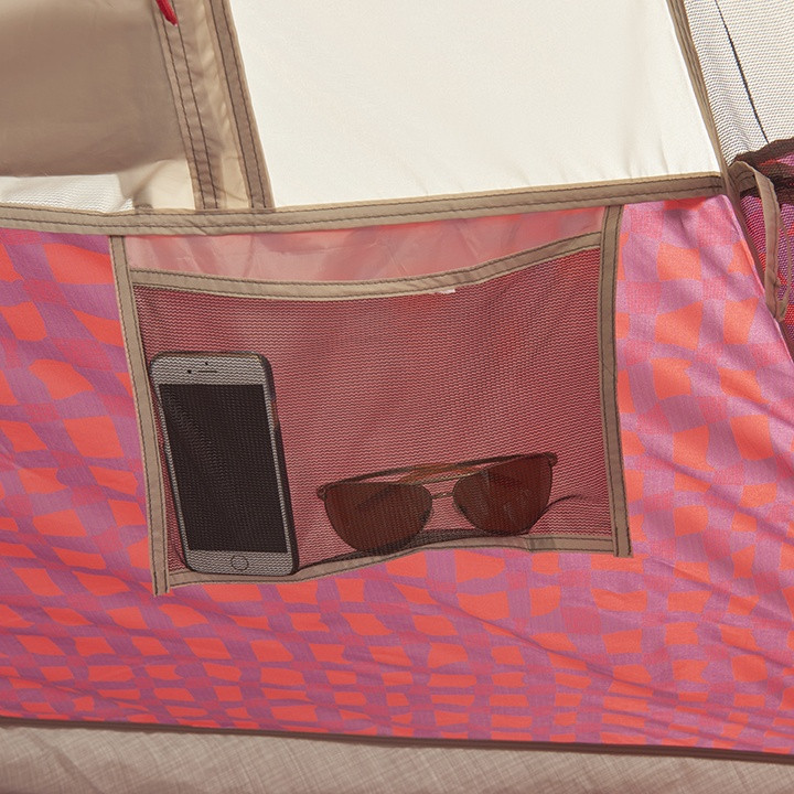 Close up view of sunglasses and a phone stored inside of a mesh storage pocket in the Wenzel Shenanigan 5 tent