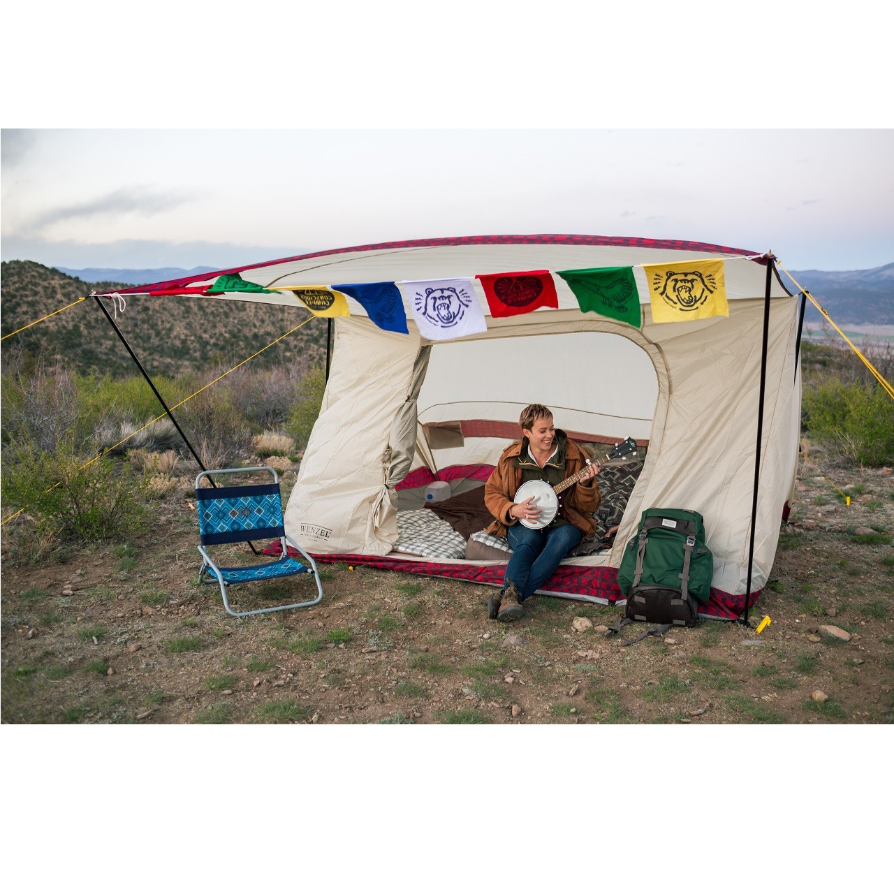 Woman sitting with her legs outside of a completely set up Wenzel Ballyhoo 4 Tent with guy lines extended playing a Banjo with a Wenzel chair and backpack outside the tent