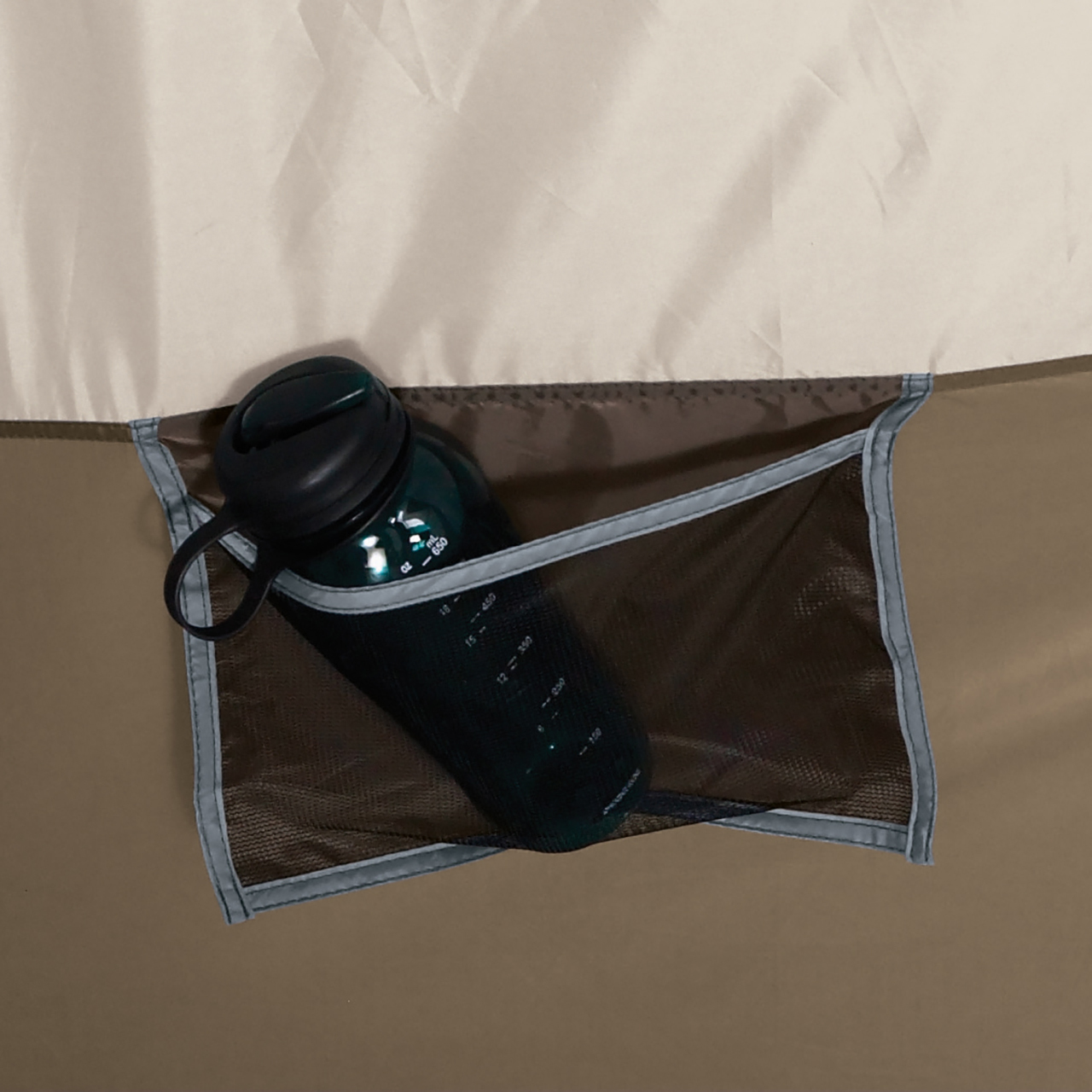 Close up view of an interior mesh pocket storing a water bottle in the Wenzel Klondike 8 tent