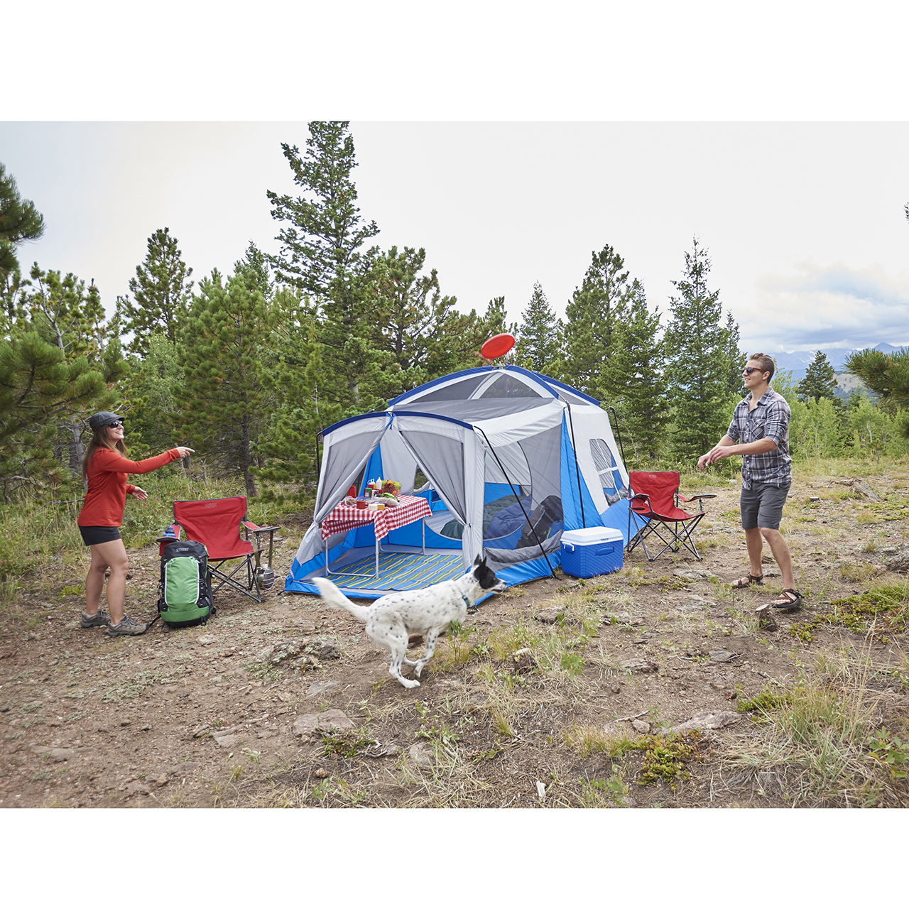 Man and woman with their dog playing Frisbee outside of a Wenzel tent setup without the rain fly on with Wenzel chairs, coolers, and backpacks outside