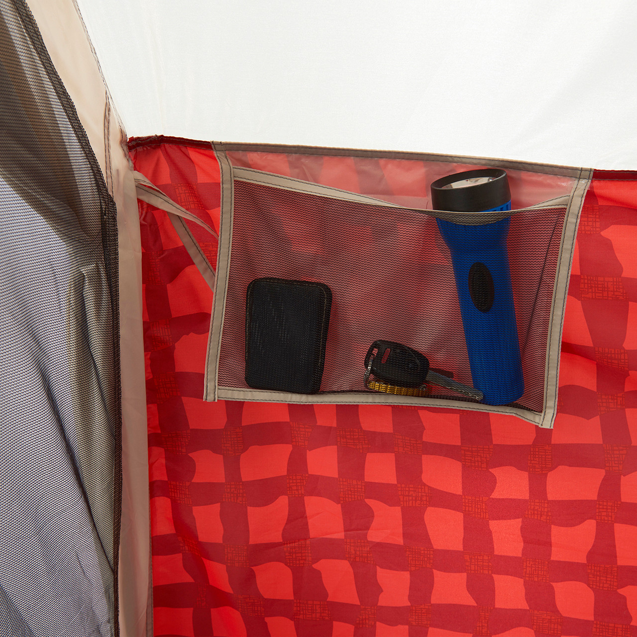 Close up view of an interior mesh pocket in the Wenzel Ivanhoe 6 tent storing a flashlight, keys, and a wallet