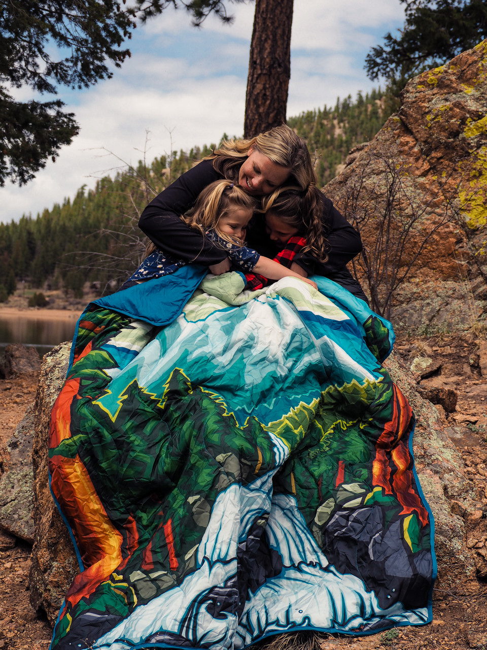 Woman outside on rocks in front of a lake wearing a Wenzel Alpine Camp Quilt around herself and two children