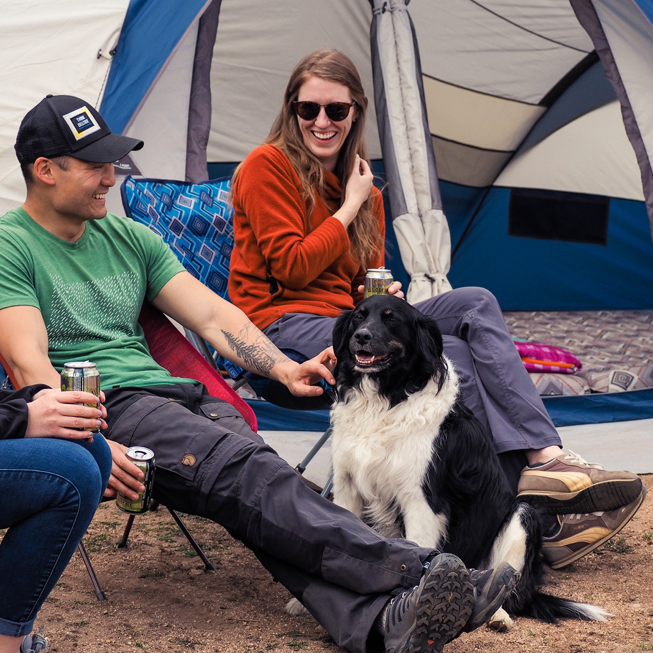 Couple with a dog in front of their tent